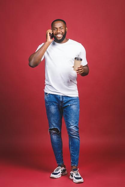 Porträt des hübschen afroamerikaners in voller länge mit handy und kaffeetasse zum mitnehmen. isoliert über rotem hintergrund. Premium Fotos