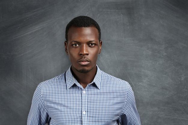 Porträt des hübschen jungen afrikanischen schullehrers, der das karierte hemd trägt, das sich für den unterricht fertig macht, sich entscheidet, mit ernstem und selbstbewusstem gesichtsausdruck schaut und an einer leeren tafel steht Kostenlose Fotos
