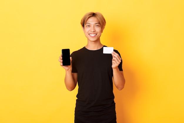 Porträt des hübschen jungen asiatischen kerls, der smartphonebildschirm, bank-app und kreditkarte zeigt, gelbe wand steht und lächelt. Kostenlose Fotos