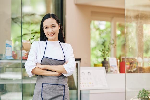 Porträt des hübschen jungen lächelnden kleinen coffeeshop-besitzers, der am eingang steht Premium Fotos