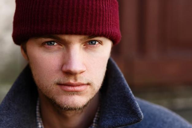 Porträt des hübschen jungen mannes im roten hut, der draußen aufwirft Kostenlose Fotos