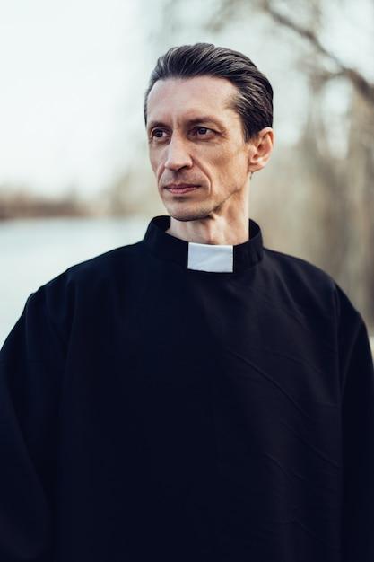 Porträt des hübschen katholischen priesters oder des pastors mit kragen Premium Fotos