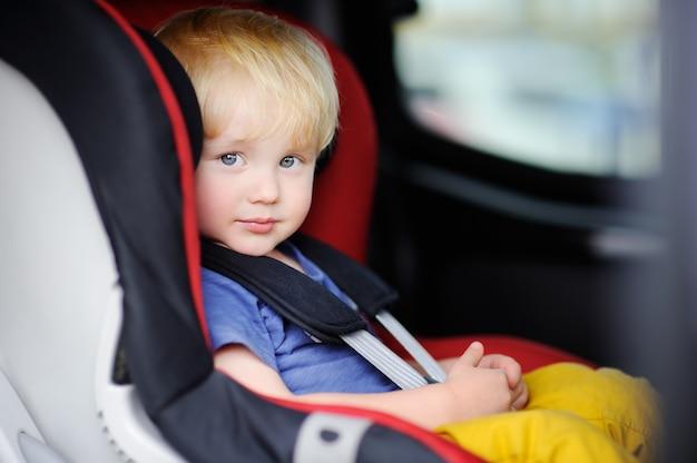 Porträt des hübschen kleinkindjungen sitzend im autositz. sicherheit beim transport von kindern Premium Fotos