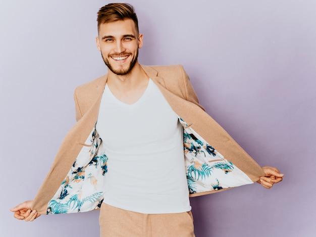 Porträt des hübschen lächelnden hippie-geschäftsmannmodells, das zufälligen beige anzug trägt. Kostenlose Fotos