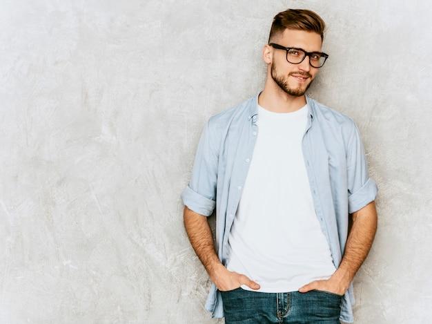 Porträt des hübschen lächelnden modells des jungen mannes, das zufällige hemdkleidung trägt. stilvoller mann der mode, der in den schauspielen aufwirft Kostenlose Fotos
