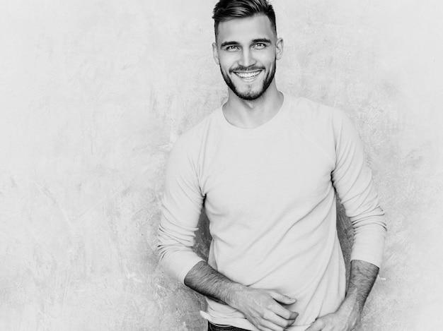 Porträt des hübschen lächelnden modells des jungen mannes, das zufällige sommerrosakleidung trägt. stilvolle mannaufstellung der mode Kostenlose Fotos