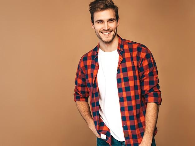 Porträt des hübschen lächelnden stilvollen modells des jungen mannes kleidete im roten karierten hemd an. mode mann posiert Kostenlose Fotos