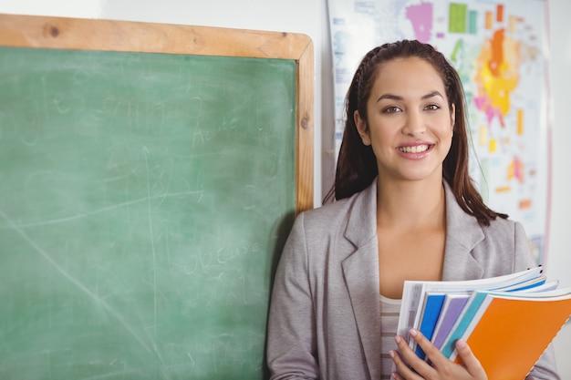 Porträt des hübschen lehrers notizblöcke in einem klassenzimmer in der schule halten Premium Fotos