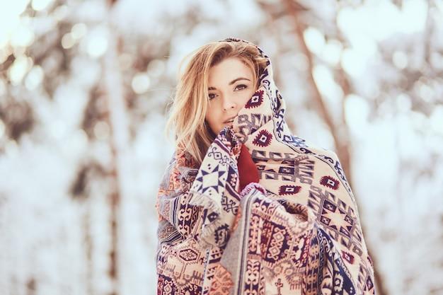 Porträt des hübschen mädchens, das in schal auf einem winterpark einwickelt Kostenlose Fotos
