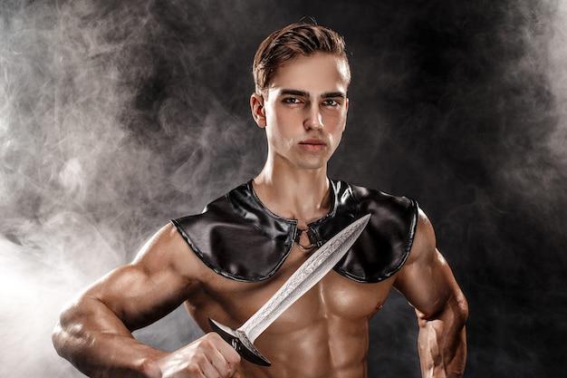 Porträt des hübschen muskulösen gladiators mit klinge. isoliert. studioaufnahme Premium Fotos