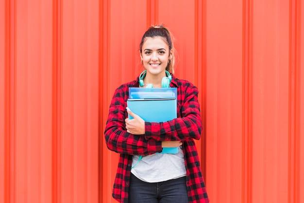 Porträt des hübschen studenten in den intelligenten zufälligen holdingbüchern in der hand, die gegen die wand schaut zur kamera steht Kostenlose Fotos