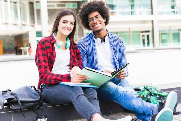 Porträt des jugendmannes und der studentinnen, die in der hand die bücher sitzen am campus halten Kostenlose Fotos
