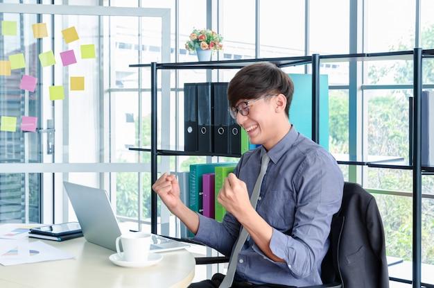 Porträt des jungen asiatischen geschäftsmannes triumphierend und feiern mit den armen oben für berufserfolg im büro Premium Fotos