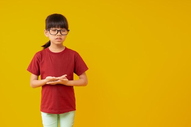 Porträt des jungen asiatischen kinderstudenten, der meditation steht und macht Premium Fotos
