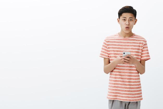 Porträt des jungen asiatischen männlichen jugendlichen mit kühler frisur im gestreiften t-shirt, das smartphone hält, das unter verwendung des neuen handy-liking-geräts aufgeregt ist, das wow mit gefalteten lippen über weißer wand sagt Kostenlose Fotos