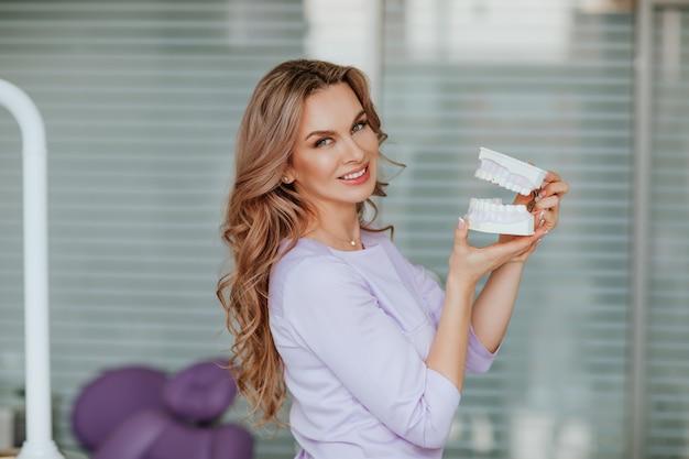 Porträt des jungen attraktiven zahnarztarztes mit dem langen lockigen haar in der violetten medizinischen uniform, die mit plastikmund im kabinett aufwirft. Premium Fotos