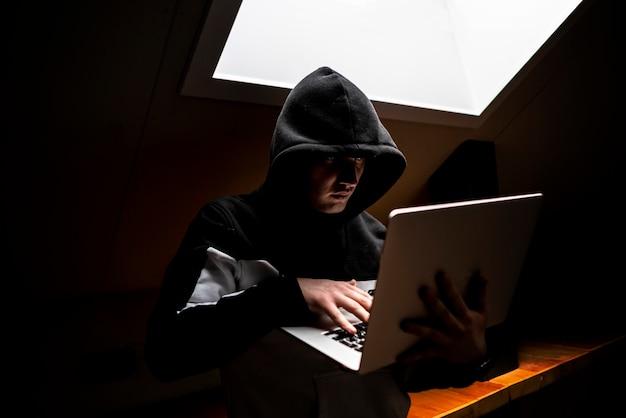 Porträt des jungen aussenseiters in der haube in der dunkelkammer mit laptop Premium Fotos
