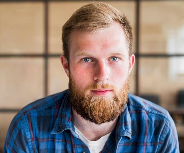 Porträt des jungen bärtigen mannes, der kamera betrachtet Kostenlose Fotos