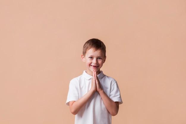Porträt des jungen betend mit einem lächeln auf seinem gesicht über beige hintergrund Kostenlose Fotos