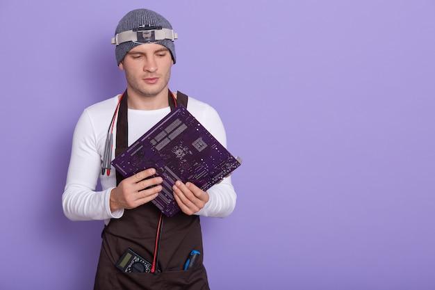Porträt des jungen erfahrenen radiotricians, der isoliert über flieder im studio steht und elektronische leiterplatte hält Kostenlose Fotos