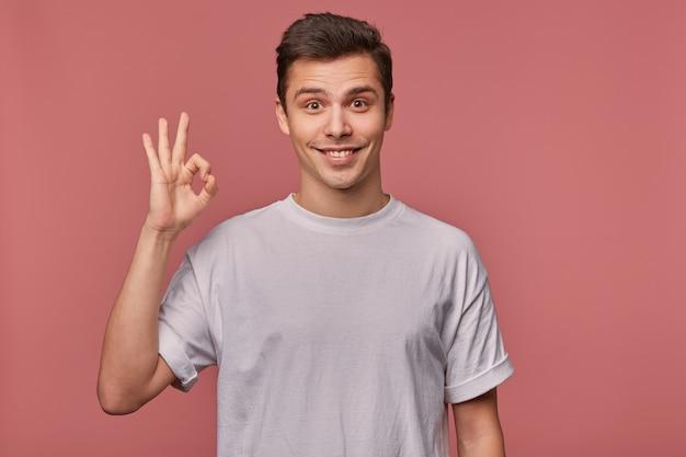 Porträt des jungen fröhlichen kerls trägt in leerem t-shirt, zeigt okey geste, steht auf rosa und breit lächelnd. Kostenlose Fotos