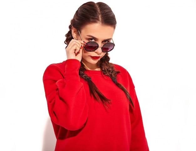 Porträt des jungen glücklichen lächelnden frauenmodells mit hellem make-up und den bunten lippen mit zwei zöpfen und sonnenbrille in der roten kleidung des sommers lokalisiert. hinter modischen sonnenbrillen Kostenlose Fotos