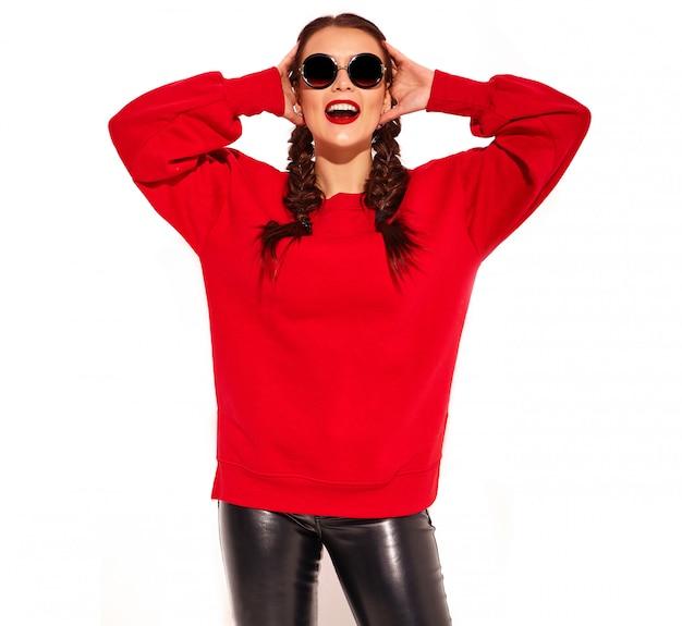 Porträt des jungen glücklichen lächelnden frauenmodells mit hellem make-up und den bunten lippen mit zwei zöpfen und sonnenbrille in der roten kleidung des sommers lokalisiert. Kostenlose Fotos