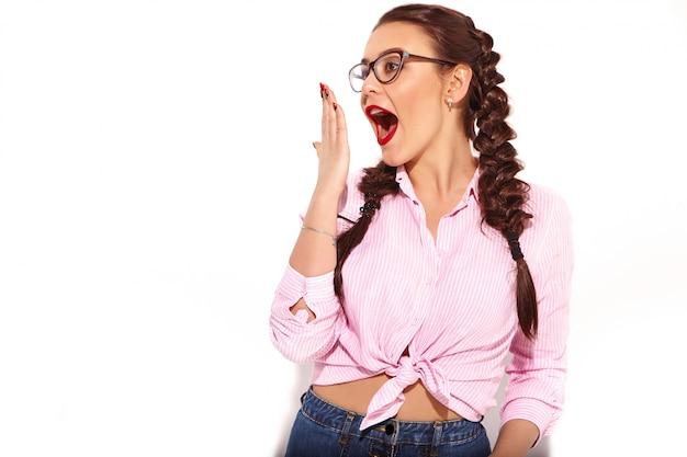 Porträt des jungen glücklichen lächelnden frauenmodells mit hellem make-up und den roten lippen mit zwei zöpfen im bunten rosa gebundenen hemd des sommers lokalisiert Kostenlose Fotos