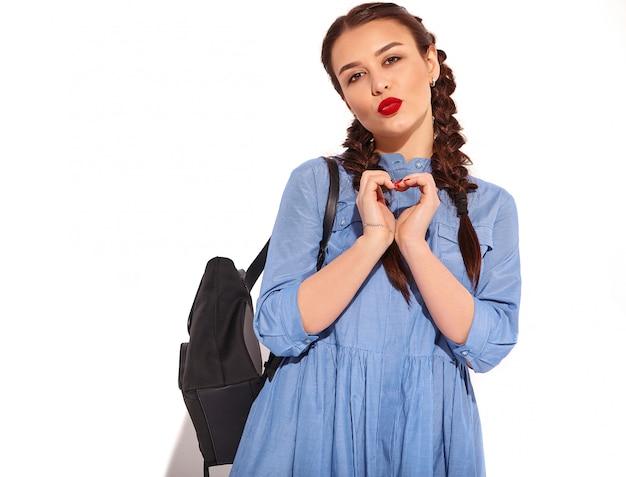 Porträt des jungen glücklichen lächelnden frauenmodells mit hellem make-up und den roten lippen mit zwei zöpfen in den händen im bunten blauen kleid und im rucksack des sommers lokalisiert. zeige herzschild Kostenlose Fotos