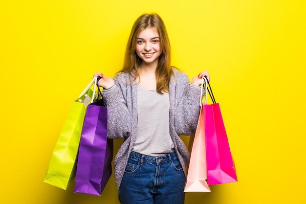 Porträt des jungen glücklichen lächelnden jugendlich mädchens mit einkaufstüten, lokalisiert Kostenlose Fotos