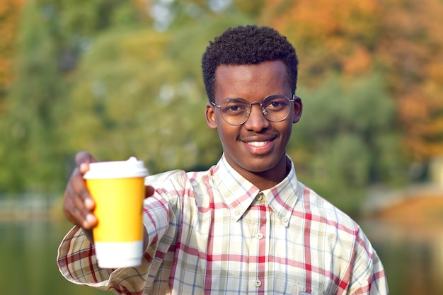 Porträt des jungen glücklichen positiven mannes im hemd und in den gläsern, die einen plastikbecher des heißen getränkes tee oder des kaffees heraushalten, lächelnd. schwarzafrikanischer afroamerikanermann im goldenen herbstpark. Premium Fotos