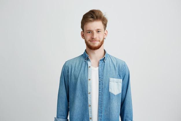 Porträt des jungen gutaussehenden mannes im jeanshemd lächelnd, das kamera betrachtet. Kostenlose Fotos