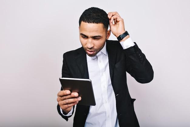 Porträt des jungen gutaussehenden mannes im weißen hemd und in der schwarzen jacke bei der arbeit mit tablette. modischer geschäftsmann, missverständnis, beschäftigt, erfolgreich, moderner lebensstil. Kostenlose Fotos
