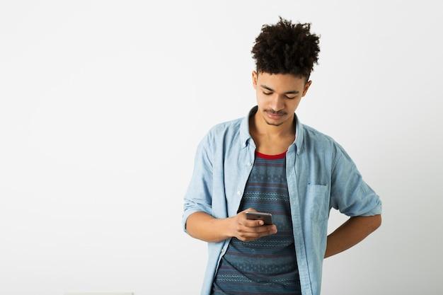 Porträt des jungen gutaussehenden schwarzen mannes, der digitales gerät hält, unter verwendung des smartphones, lokalisiert auf weißem hintergrund, afroamerikanische jugend, hipster-stil, student, beschäftigt Kostenlose Fotos