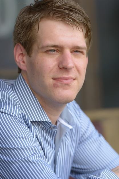 Porträt des jungen hübschen blonden geschäftsmannes, der am kaffeehaus draußen entspannt Premium Fotos