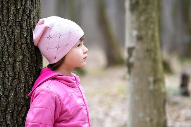 Porträt des jungen hübschen kindermädchens, das rosa jacke und mütze trägt, die an einen baum im wald lehnen, der warmen warmen tag im frühen frühling draußen genießt. Premium Fotos