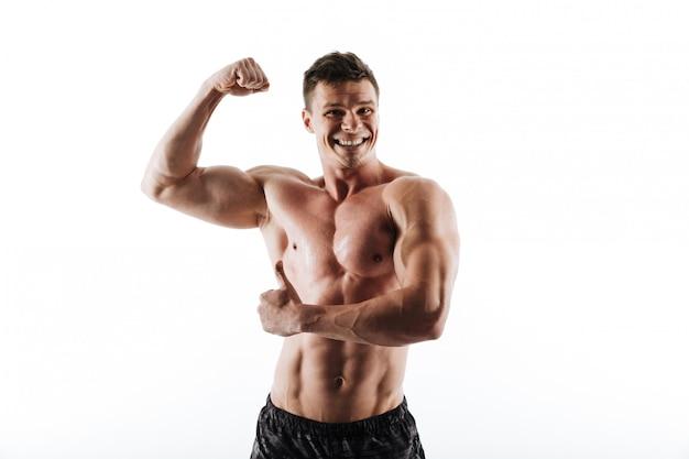 Porträt des jungen lachenden muskulösen mannes, der seinen bizeps und daumen hoch geste zeigt Kostenlose Fotos