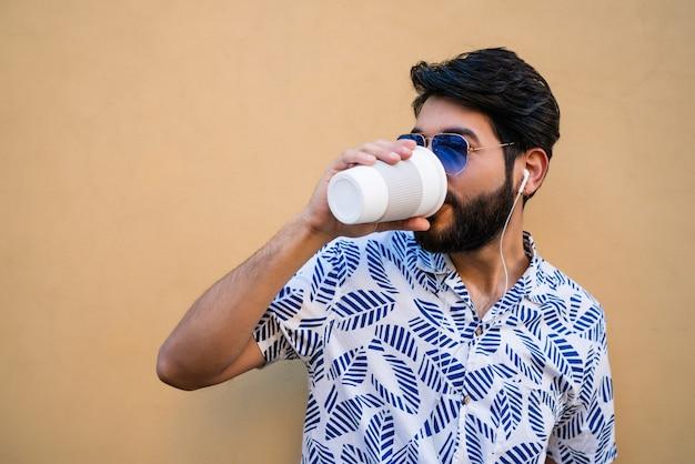 Porträt des jungen lateinischen mannes, der sommerkleidung trägt, eine tasse kaffee trinkt und musik mit kopfhörern gegen gelben raum hört. Kostenlose Fotos