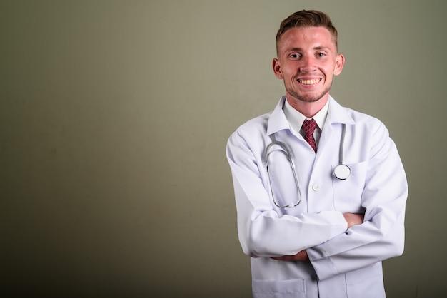 Porträt des jungen mannarztes gegen farbige wand Premium Fotos