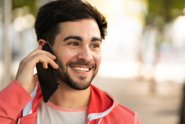 Porträt des jungen mannes, der am telefon spricht, während er draußen auf der straße steht. stadtkonzept. Kostenlose Fotos
