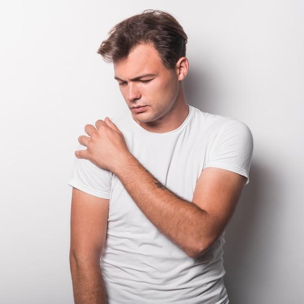 Porträt des jungen mannes, der die schmerz in der schulter steht gegen weißen hintergrund hat Kostenlose Fotos