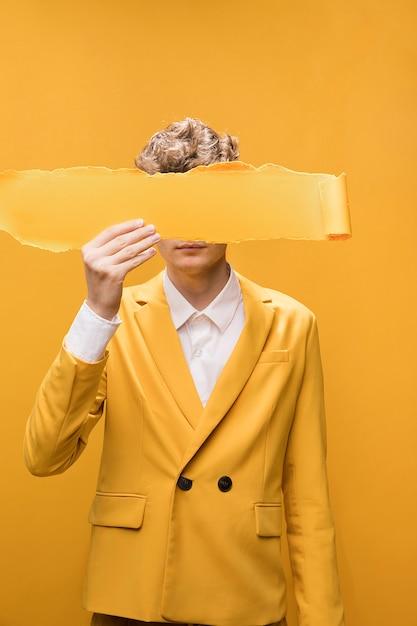 Porträt des jungen mannes in einer gelben szene mit heftigem papier vor gesicht Kostenlose Fotos