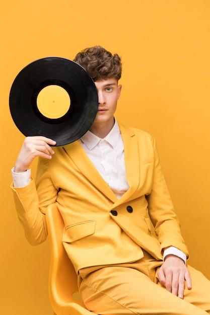 Porträt des jungen mannes mit einem vinyl in einer gelben szene Kostenlose Fotos
