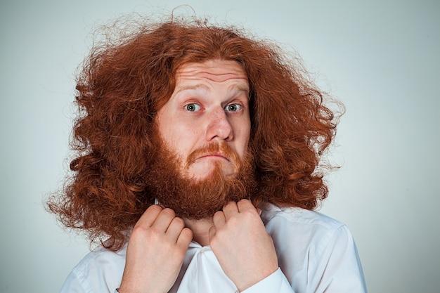 Porträt des jungen mannes mit langen roten haaren und mit geschocktem gesichtsausdruck auf grau Kostenlose Fotos