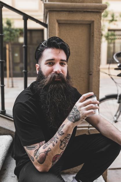 Porträt des jungen mannes mit tätowierung auf seiner hand, die kaffeetasse hält Kostenlose Fotos