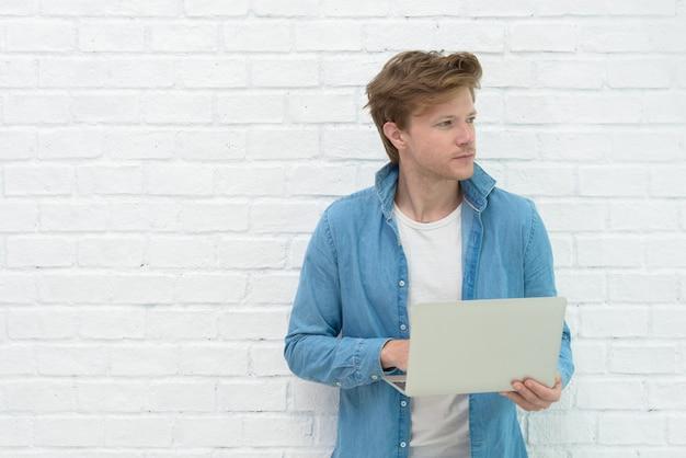 Porträt des jungen mannes stehend, laptop halten und medien mit glücklichem lächeln aufpassen Premium Fotos