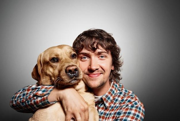 Porträt des jungen mannes und seines niedlichen hundes Kostenlose Fotos