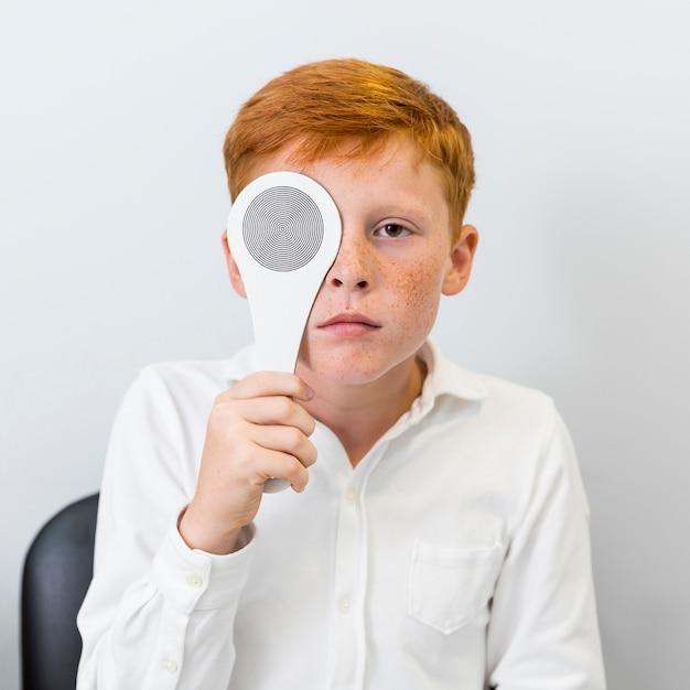 Porträt des jungen mit der sommersprosse, die okkluder vor seinem auge hält Kostenlose Fotos