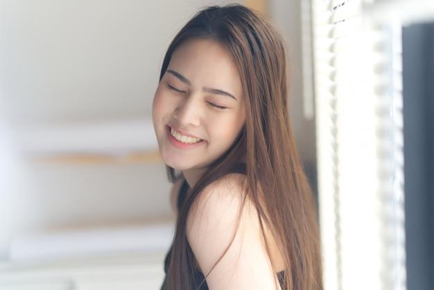 Porträt des jungen netten asiatischen mädchens, das ihre augen mit dem lächeln steht nahe bei dem fenster schließt Premium Fotos