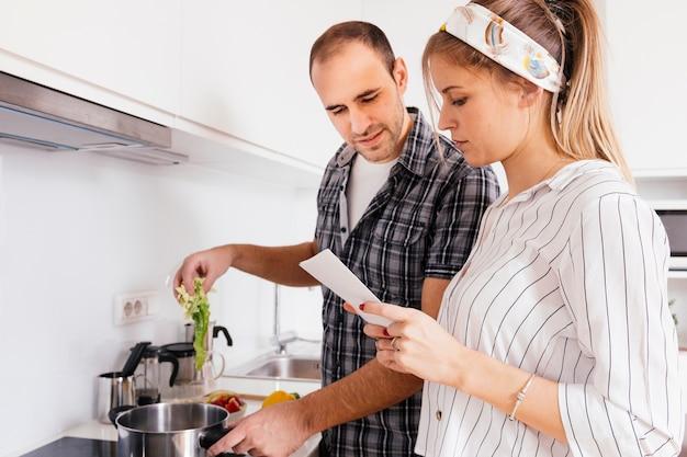 Porträt des jungen paarleserezeptbuches beim an der küche zusammen kochen Kostenlose Fotos